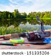 fishing tackle on a pontoon on the background of the lake in the woods - stock photo