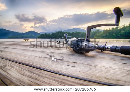 fishing tackle on a wooden float with mountain background and selective focus - stock photo