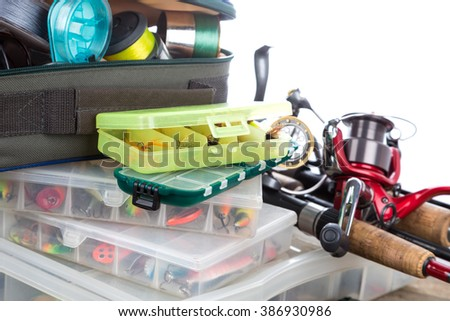 fishing tackles and baits in box and bag on wooden boards background for outdoor active business - stock photo