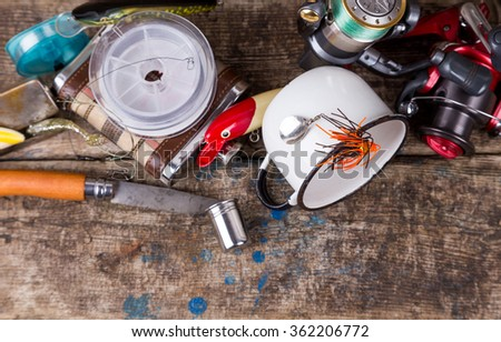 fishing tackles and baits with white metal cup on background of wooden timbers