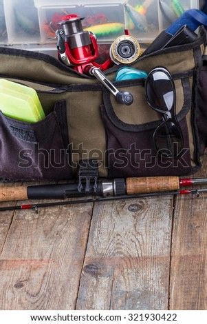 fishing tackles and lures in open handbag on wooden background. for design advertising or publication