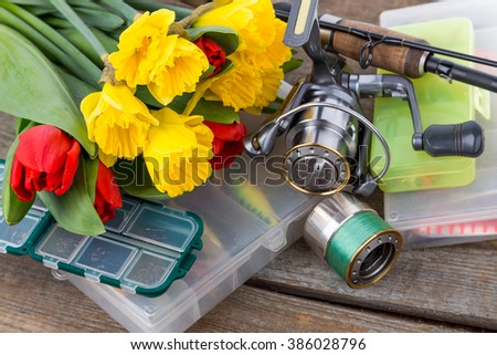 fishing tackles with bouquet of spring flowers narcissus and tulips on wooden background for outdoor active business for women gift - stock photo