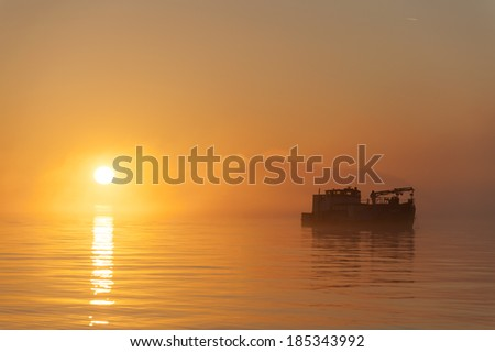 Fishing Tender at Sunset. A fishing tender, or buyer boat, in the Puget Sound waters heads home to unload the salmon catch of the day at the cannery. - stock photo