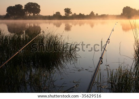 fishing time... rods and lake... sunerise - stock photo