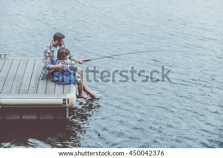 Fishing together. Top view of father and son fishing together while sitting on quayside - stock photo