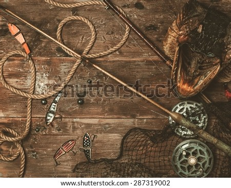 Fishing tools and pike's head on a wooden table - stock photo