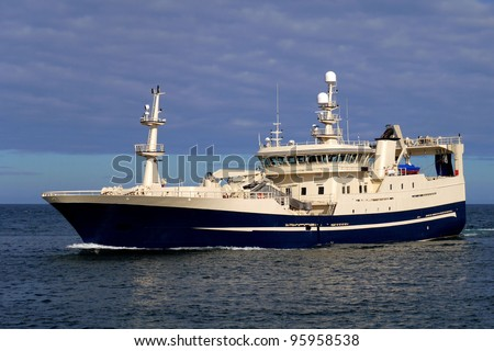 Fishing Trawler underway fully loaded. - stock photo