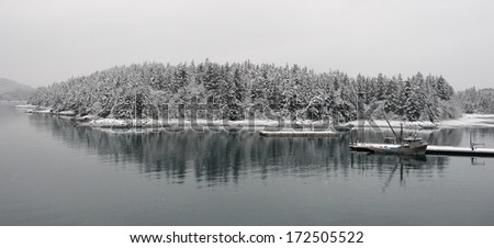 Fishing vessel at the snow-covered mooring - stock photo