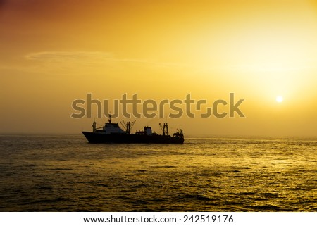 Fishing vessel for fishing in the sea. Sunset. Calm weather. Several ships.