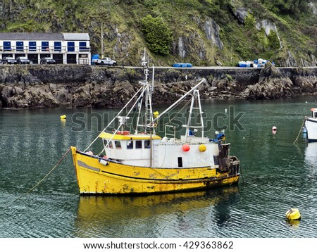 Fishing vessel moored in harbor; small commercial fishing boat moored in rural harbor  - stock photo