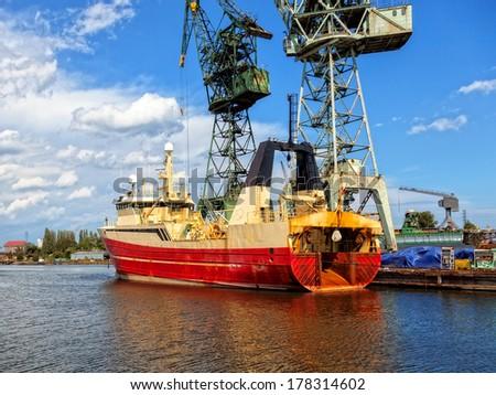 Fishing vessel trawler in a repair yard. - stock photo