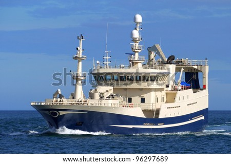 Fishing vessel underway at sea over blue sky and sea. - stock photo