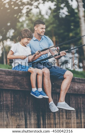 Fishing with father. Cheerful father and son fishing while sitting on quayside