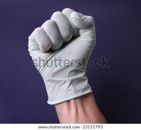 Fist in medical glove - stock photo