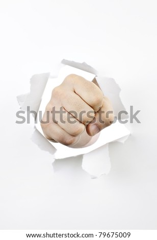Fist punching through hole in white paper - stock photo
