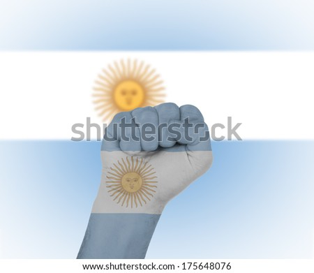 Fist wrapped in the flag of Argentina and flag in the background - stock photo