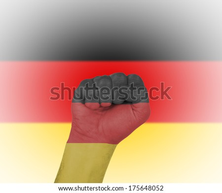 Fist wrapped in the flag of Germany and flag in the background - stock photo