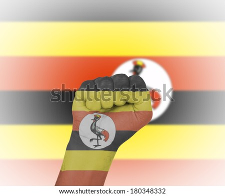 Fist wrapped in the flag of Uganda and flag in the background - stock photo