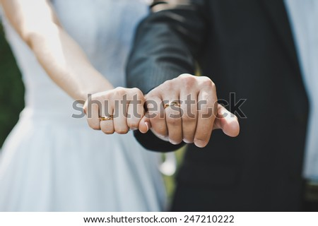 Fists of the newly-married couple with wedding rings in them. - stock photo