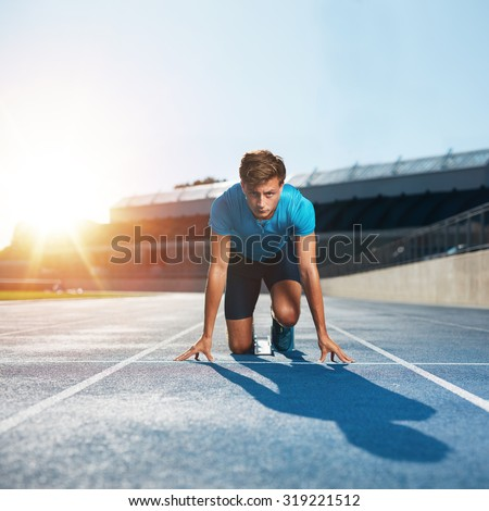 Fit and confident man in starting position ready for running. Male athlete about to start a sprint looking at camera with bright sunlight. - stock photo