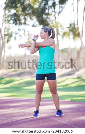 Fit and happy female athlete doing stretches before she starts training on a tartan athletics track. - stock photo