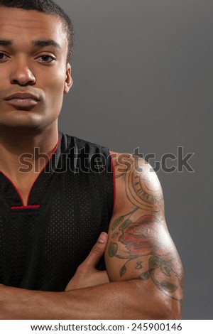 Fit and strong. Handsome young African man looking at camera and holding his hands crossed while standing against grey background - stock photo