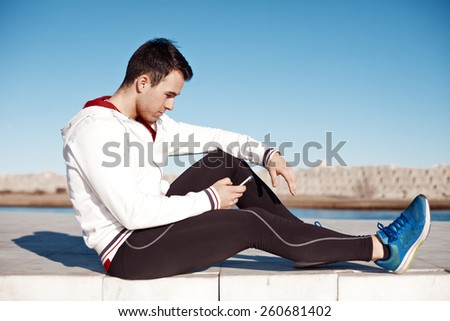 fit athlete sitting outdoors and typing message with smartphone