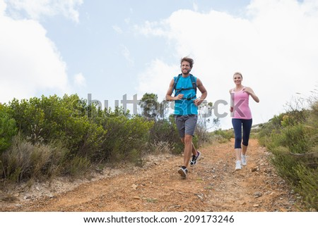 Fit attractive couple jogging down mountain trail on a sunny day - stock photo
