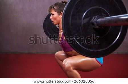 Fit attractive female athlete in sexy outfit performs barbell squat in gym. - stock photo
