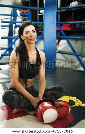 Fit attractive woman with gloves sits on boxing ring in gym