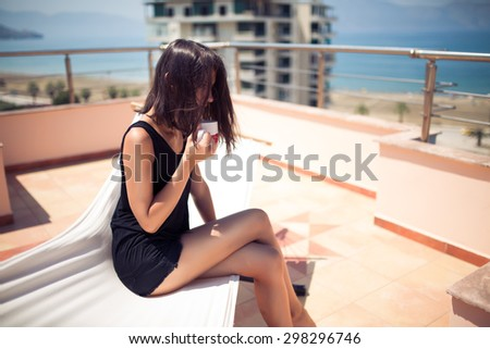 Fit attractive young woman sitting on terrace in hammock drinking coffee beverage i the morning at the seaside - stock photo