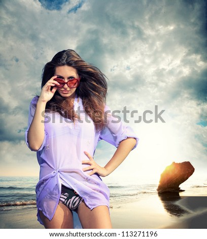 Fit beautiful woman in tropical beach dramatic cloudscape on background - stock photo