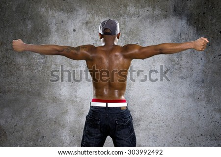 Fit black man in hip hop style clothing flexing back muscles. He is shirtless to show off his muscles and has a tattoo on one arm.