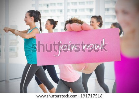 Fit blonde holding card saying join now against fitness class in gym - stock photo