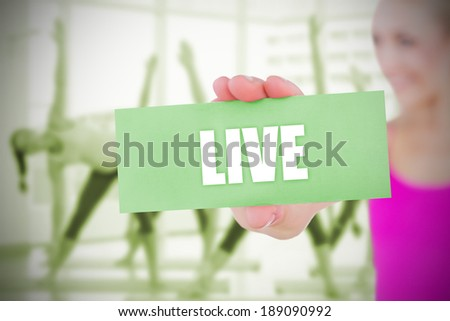 Fit blonde holding card saying live against fitness class in gym - stock photo