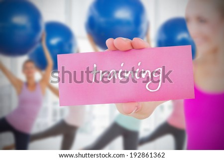 Fit blonde holding card saying training against fitness class in gym - stock photo