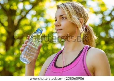 Fit blonde holding her water bottle on a sunny day - stock photo