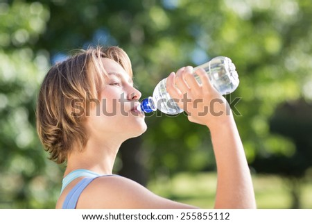 Fit blonde in the park drinking water on a sunny day - stock photo