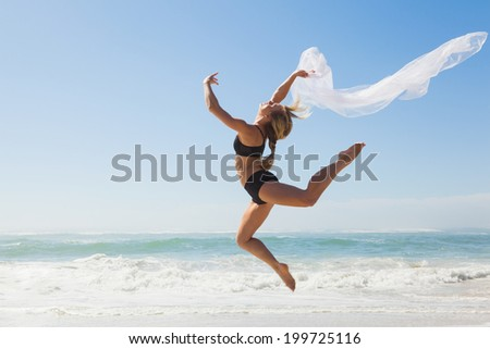 Fit blonde jumping gracefully with scarf on the beach on a sunny day - stock photo