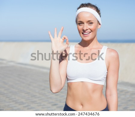 Fit blonde smiling on the pier on a sunny day