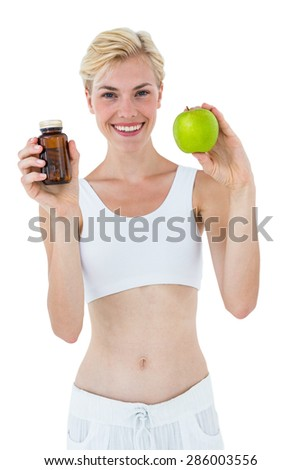 Fit blonde woman holding medicine and green apple on white background - stock photo