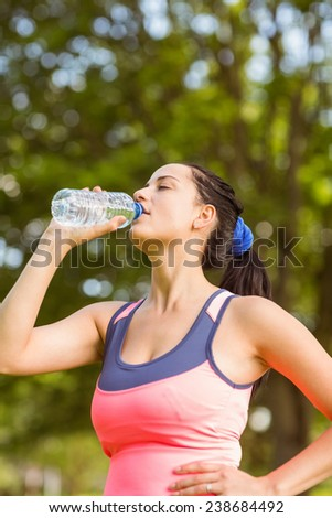 Fit brown hair drinking from her water bottle in the park