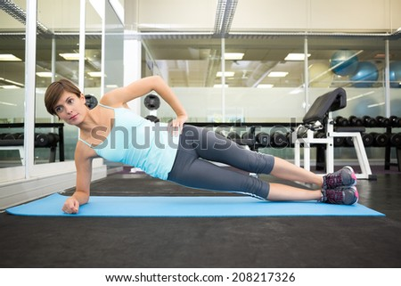 Fit brunette doing pilates on exercise mat at the gym - stock photo