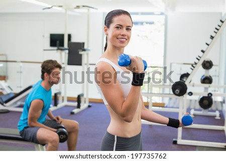 Fit brunette exercising with blue dumbbells smiling at camera at the gym