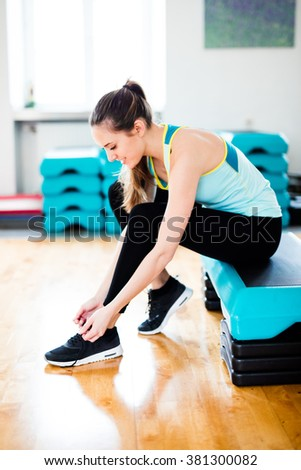 Fit Brunette Girl with Black Shoes, Black Legging and Blue and Yellow Sports Outfit and Shirt at the Gym working on her Fitness - stock photo