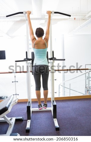 Fit brunette hanging from bars at the gym