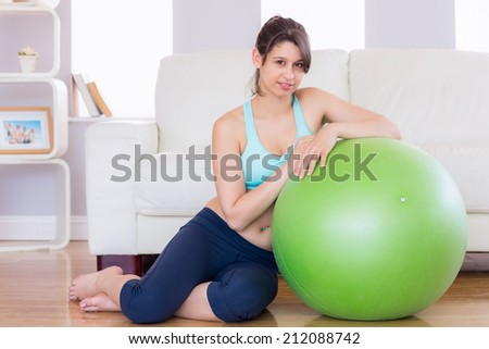 Fit brunette leaning on exercise ball smiling at camera at home in the living room - stock photo