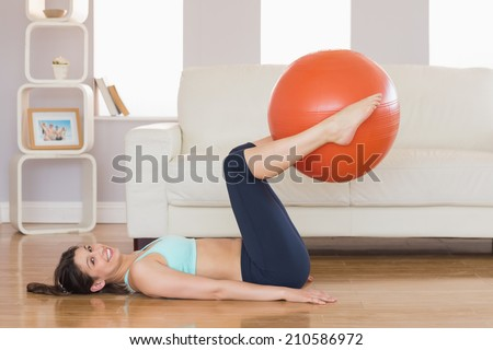 Fit brunette lifting exercise ball with legs at home in the living room - stock photo