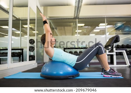 Fit brunette using bosu ball to work out at the gym - stock photo
