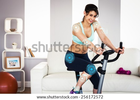Fit brunette working out on exercise bike against fitness interface - stock photo